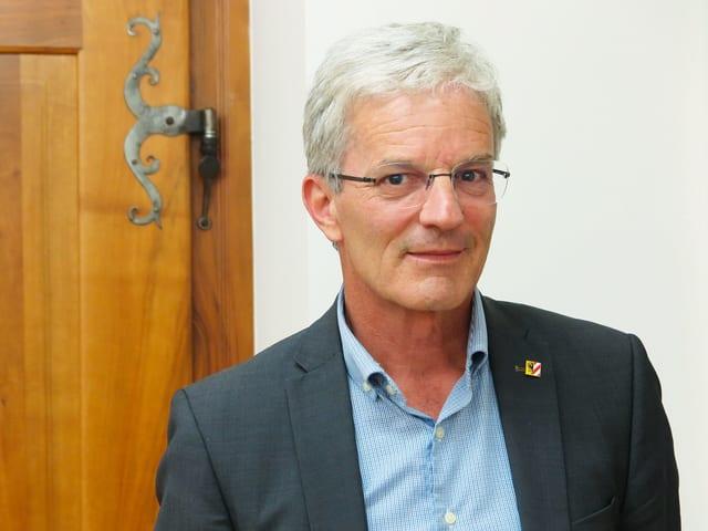 Porträtbild eines 60-jährigen grauhaarigen Politikers mit blauem Veston und Brille.