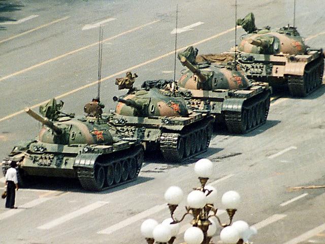 Ein Mann steht ganz alleine vor vier Panzern.