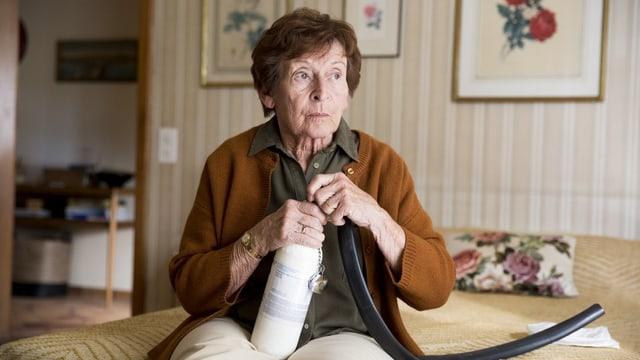 Eine ältere Frau sitzt auf ihrem Bett und schaut ernst drein. Sie hantiert mit einer Gasflasche und einem Schlauch.