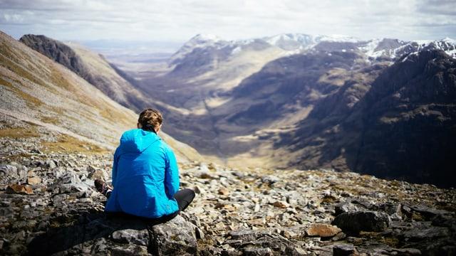 Frau sitzt auf Steinen und schaut in die Berge.