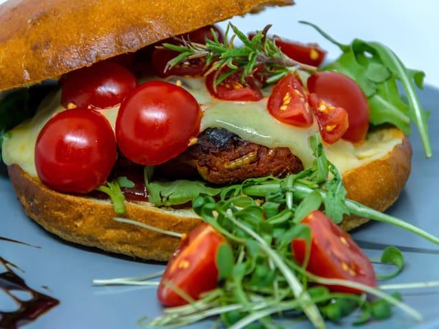 Ein Hamburger mit Cherrytomaten, Käse, Rucola und Käfern.