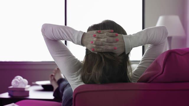 Eine Frau entspannt sich auf einem Sofa. Man sieht sie von hinten.