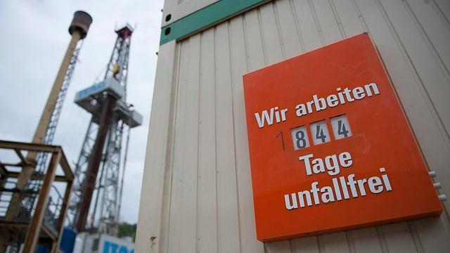 Im Hintergrund ein Bohrturm. Im Vordergrund ein Schild mit der Aufschrift: «Wir arbeiten 844 Tage unfallfrei»