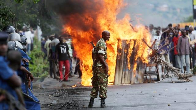 Eine Menschenmenge hat auf der Strasse ein Feuer entfacht.