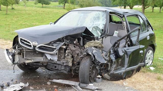 Der schwarze Nissan ist stark beschädigt, sowohl an der vorderen wie auch an der linken Seite.