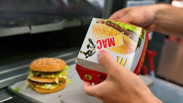 Mann verpackt Burger