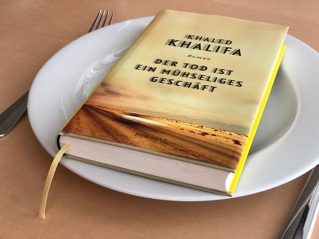 Der Roman «Der Tod ist ein mühseliges Geschäft» von Khaled Khalifa liegt auf einem weissen Teller
