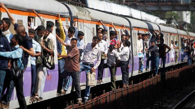 Personen lehnen aus Türen eines Zugs