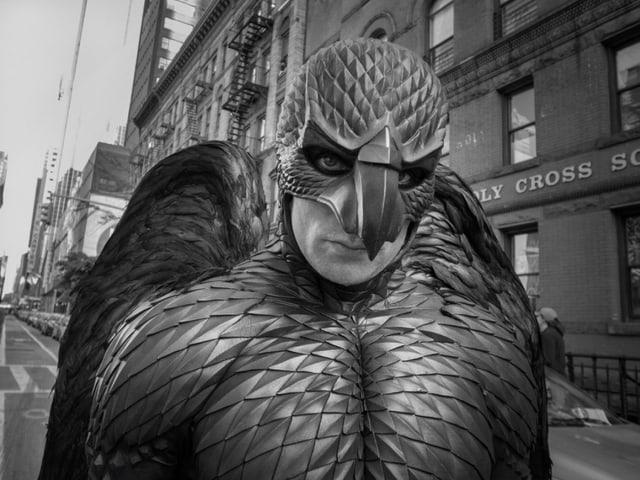 Ein Mann, der als Adler verkleidet ist, schaut in die Kamera.