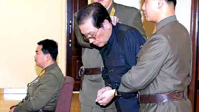 Kim Jong Uns Onkel Jang Song Thaek wird von zwei Polizisten abgeführt.
