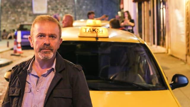Der Taxifahrer steht vor seinem gelben Taxi.