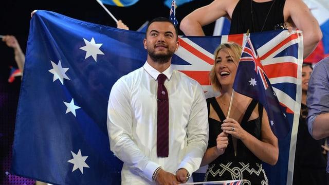 Mann und Frau stehen vor Flagge und lachen.