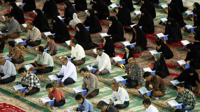 Jungen und Männer, dahinter Frauen sitzen auf Gebetsteppichen und lesen.