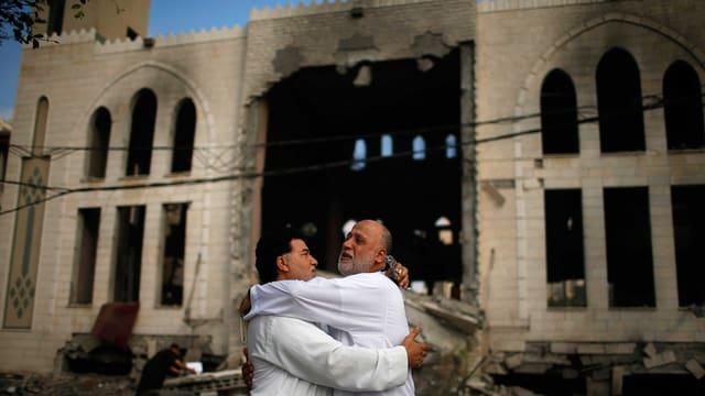 Zwei Männer umarmen sich vor einer zerbombten Moschee.
