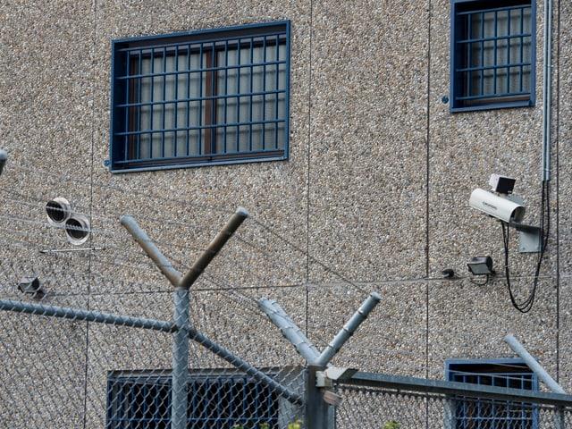 Eine Kamera, die auf ein vergittertes Fenster mit blauen Gittern gerichtet ist.