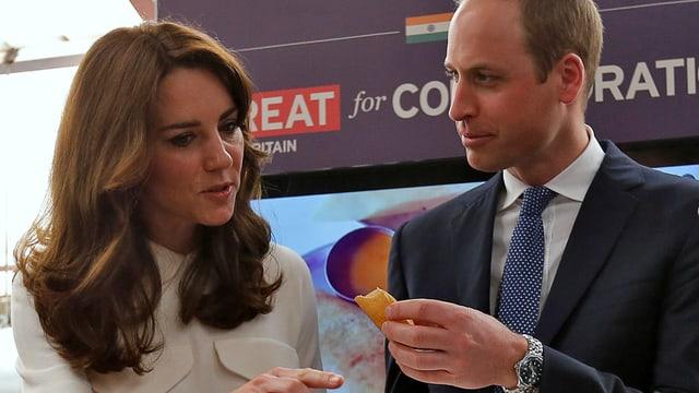 Kate und William unterhalten sich, während William eine Frühlingsrolle in der Hand hält.