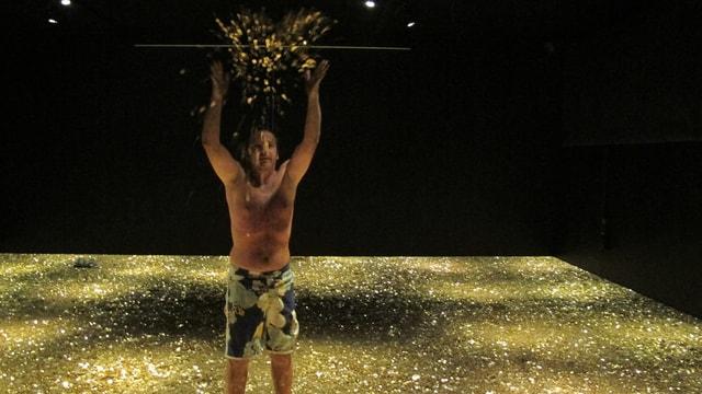 Ein Mann in Badehose steht in einem Berg aus goldenen Münzen.