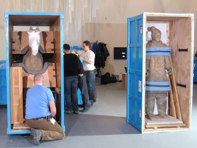 Zwei Kisten stehen geöffnet, in derjenigen rechts ein noch angebundener Tonsoldat, links ein Pferd.