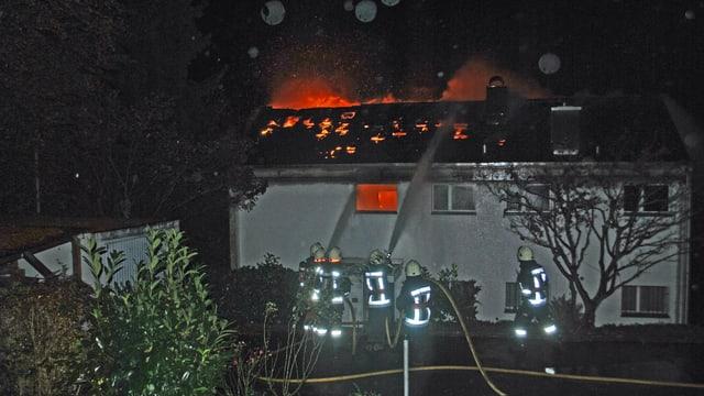 Feuerwehrleute vor brennendem Haus.