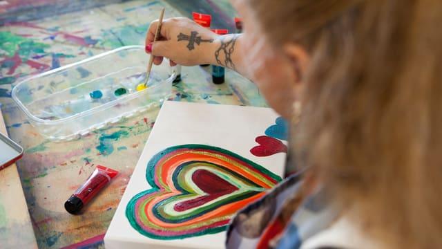 Eine Frau tunkt einen Pinsel in Farbe. Sie sitzt vor einer Leinwand, auf der verschiedene Herzen gemalt sind.