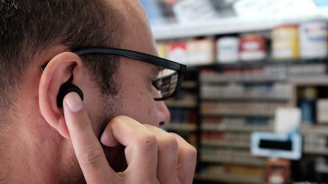 Ein Kopf mit Ohr, darin ein Here One-Knopf und eine Hand, die darauf tippt. Das ganze in einem Kiosk vor der Kasse.