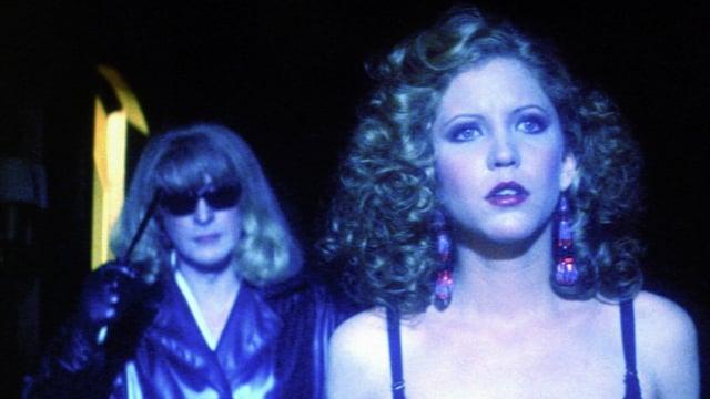 Eine blonde Frau mit Sonnebrille nähert sich von hinten einer anderen Blondine mit Messer in der Hand.