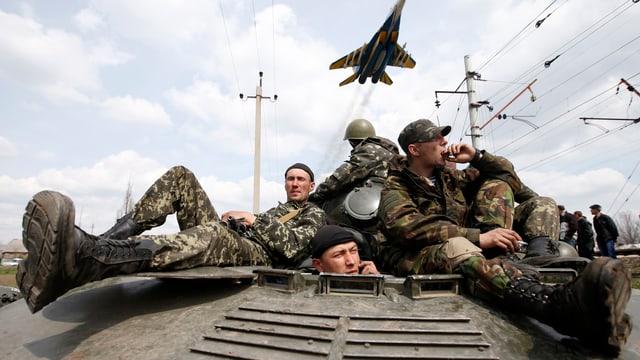 Ukarinische Soldaten sitzen auf einem Panzer und strecken ihre Beine