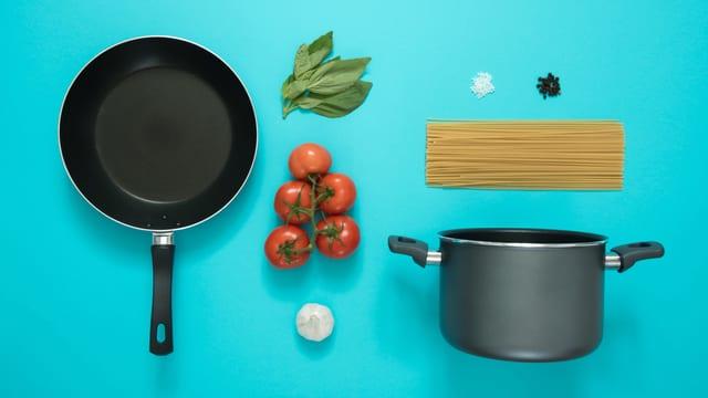 Die Zutaten für Spaghetti mit Tomatensauce auf blauem Hintergrund