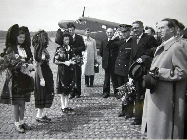 Auf einem historischen Bild stehen Politiker, Piloten und Frauen in Trachten vor einem Flugzeug.