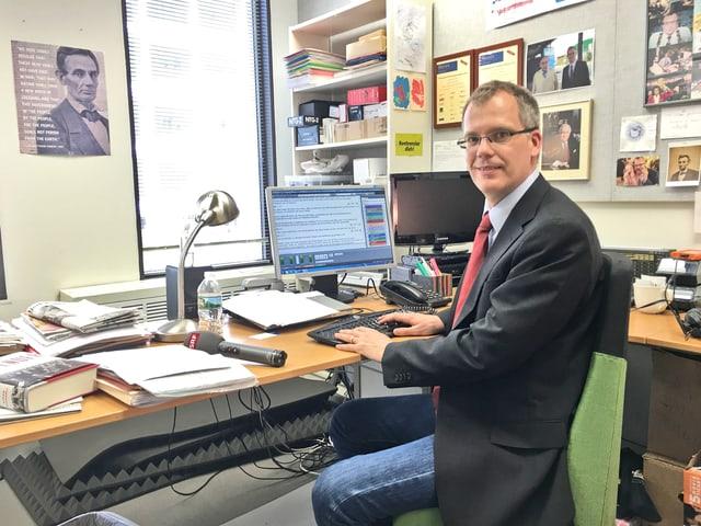 Büro mit Korrespondenten und Schreibtisch und Computer, viele Bilder an der Wand.