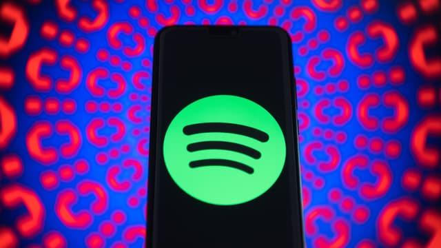 Handy, auf dem das Spotify-Logo zu sehen ist, vor einem bunten Hintergrund