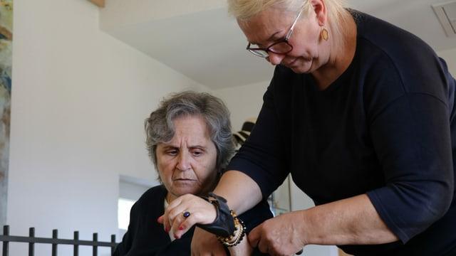 Die Pflegefachkraft hilft der alten Frau den Pullover anzuziehen.