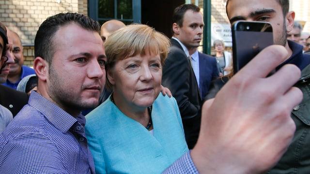 Ein Flüchtling macht ein Selfie mit Kanzlerin Angela Merkel