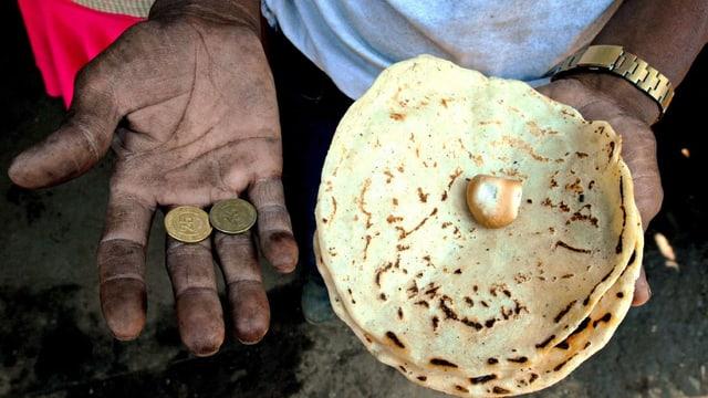Ein Mann aus Nicaragua hält in der einen Hand Münzen, in der anderen ein Fladenbrot.