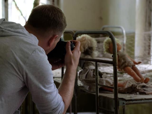 Mann macht Foto von Bett mit Pupen.