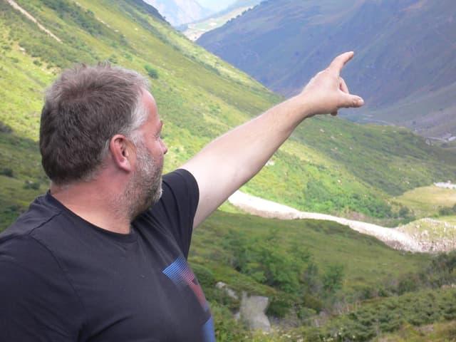 Ein Älpler zeigt auf einer Alp in die Ferne.