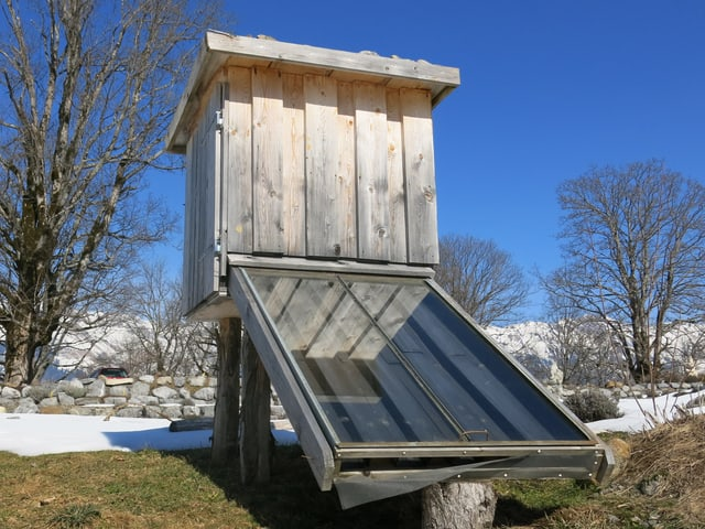 Ein Häuschen auf Stelzen mit Wärmesammel-Element davor
