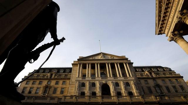 Bild der Fassade der Bank of England (BoE) aus der Froschperspektive. Am linken Bildrand ist ein Wachmann mit Sturmgewehr zu sehen.