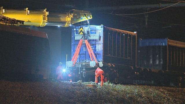 Kran hebt Zugwagen hinter der entgleisten Lokomotive an.