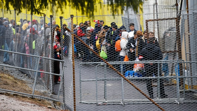 Grenzzaun mit Schlange wartender Menschen