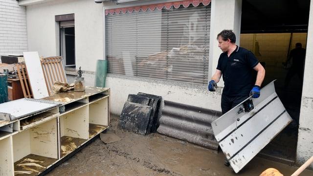Mann trägt Metallteil aus überflutetem Ladenlokal