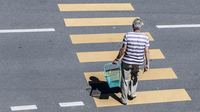 Ein Mann geht mit Einkaufskorb in der Hand über einen Fussgängerstreifen.