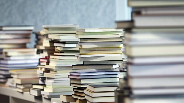 Auf einem Tisch stapeln sich Bücher.