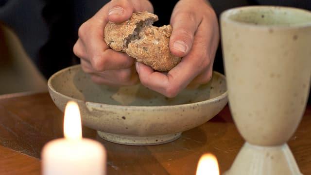 Ein Keramikbecher, zwei Hände, die über einer Keramikschale ein Brot brechen.