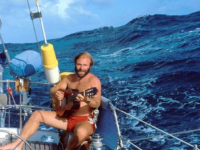 Mann sitzt auf Segelschiff im Hintergrund wirft das Meer hohe Wellen.