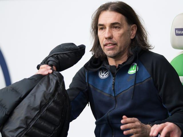 Martin Schmidt mit einer Jacke in der Hand.