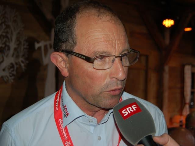 Ein Mann mit Brille und hellblauem Hemd.