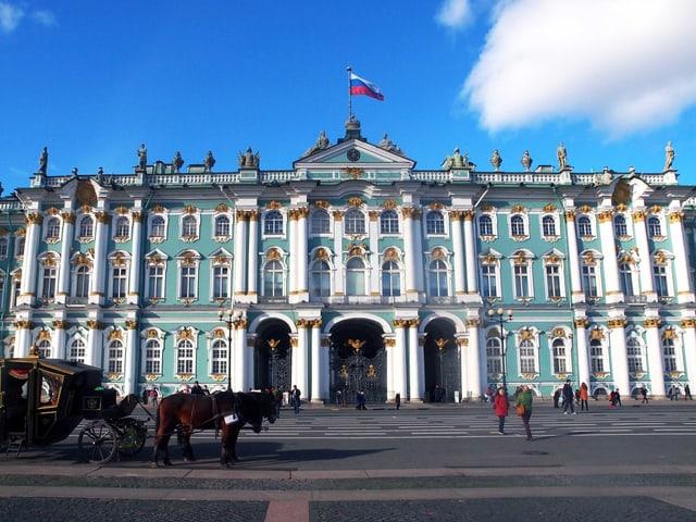 Der Winterpalast unter strahlend blauem Himmel: Vor dem weiss-türkis-goldenen Gebäude steht eine Kutsche.