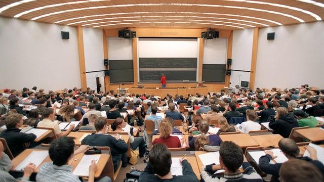 Sala da prelecziun cun students che guardan giu tar il dozent.