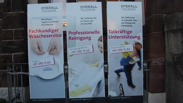 Drei Plakate, auf denen die Arbeit von Overall angepriesen wird.